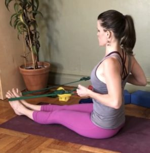 Laurel seated on yoga mat using resistance band