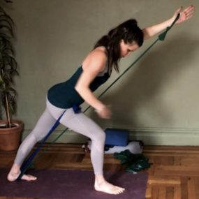 Laurel standing using resistance bands with arms and foot